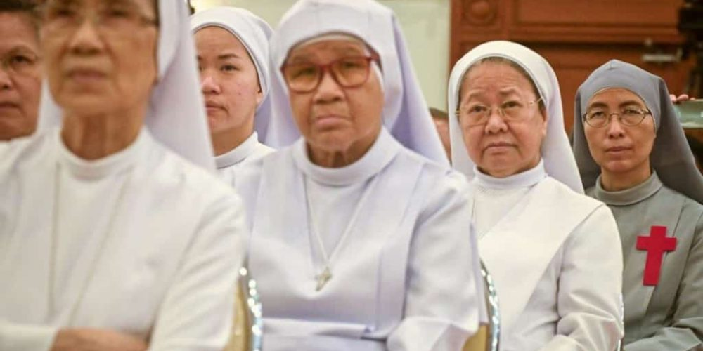 Nuns listen to announcement of the Pope coming to Thailand. Thailand Event Guide